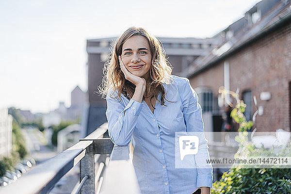 Geschäftsfrau steht auf ihrem städtischen Dachgarten