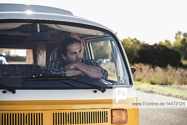 Young man on a road trip with his camper  taking a break  relaxing