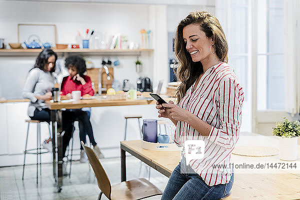 Smiling woman with cell phone at table