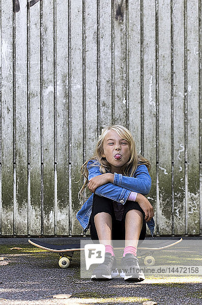 Portrait of girl sitting on skateboard in front of wooden wall sticking out tongue