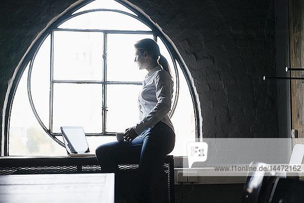 Geschäftsfrau mit Laptop und Tasse Kaffee am Fenster