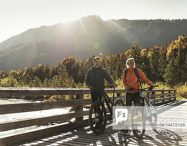 Österreich  Alpen  Paar mit Mountainbikes über eine Brücke