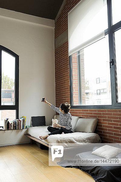 Junge Frau sitzt zu Hause auf dem Sofa  isst asiatisches Essen zum Mitnehmen und nimmt sich ein Selfie