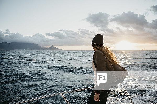 Südafrika  junge Frau mit Wollmütze während einer Bootsfahrt bei Sonnenuntergang