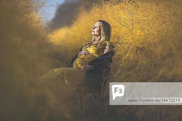 Schwangere Frau sitzt im Herbst auf einem Stuhl im Spargelfeld