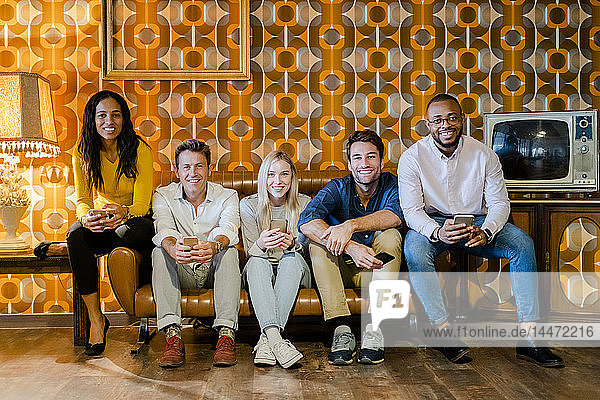 Group of smiling people sitting on couch in vintage living room holding cell phones