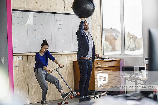 Ein reifer Mann und sein Assistent spielen mit einem Roller und stehen im Büro vor dem weißen Brett