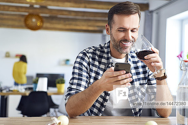 Man sitting at table  using smartphone  relaxing with a glass of red wine