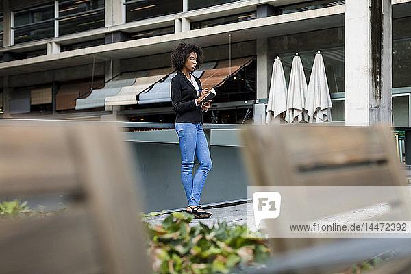 Geschäftsfrau steht auf der Terrasse und macht Notizen