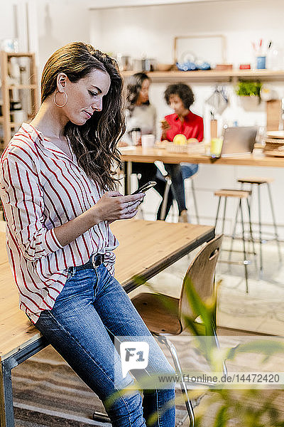 Woman with cell phone at table