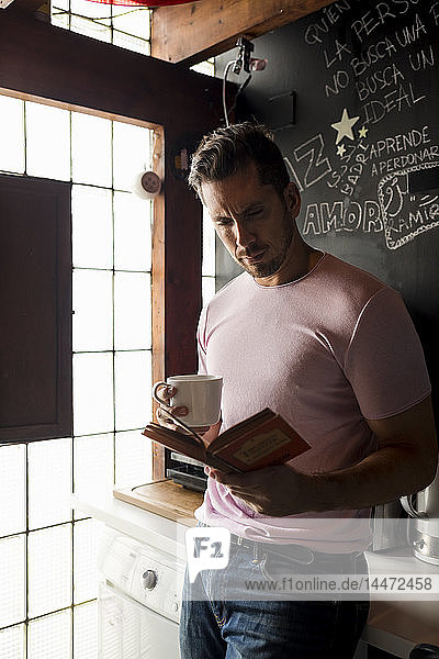 Man with cup of coffee reading a book in kitchen