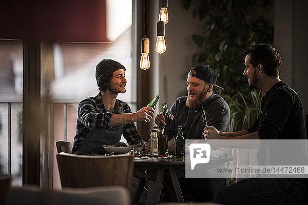 Freunde trinken Bier und essen gemeinsam  was sie gekocht haben