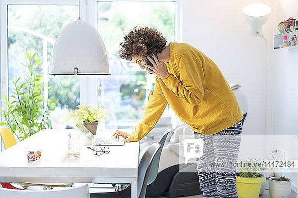 Frau benutzt Laptop und Handy auf dem Tisch zu Hause