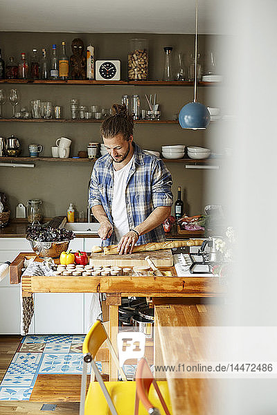 Young man preparing food at home  slicing bread