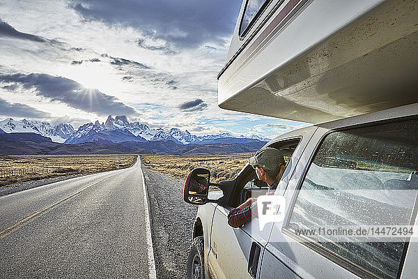 Argentina  Patagonia  El Chalten  woman looking out of window in camper on road towards Fitz Roy