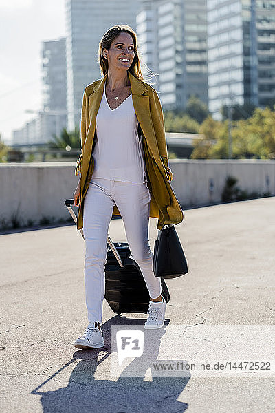 Smiling woman with suitcase and handbag in the city on the go