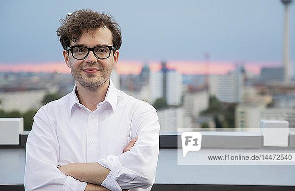 Deutschland  Berlin  Porträt eines erfolgreichen Geschäftsmannes auf der Dachterrasse bei Sonnenuntergang