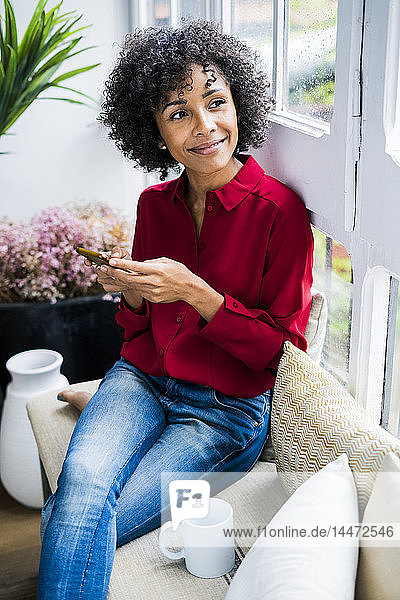 Smiling woman sitting at the window at home with cell phone