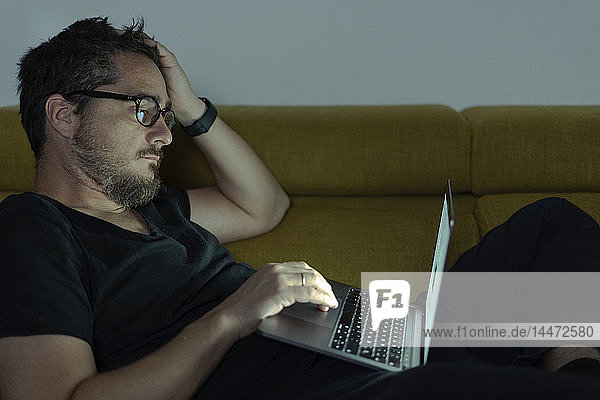 Man lying on couch using laptop at night