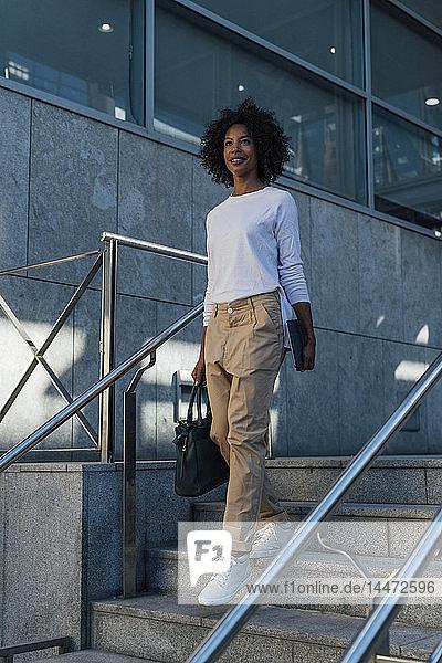 Junge lockere Geschäftsfrau mit Tablett auf Stufen