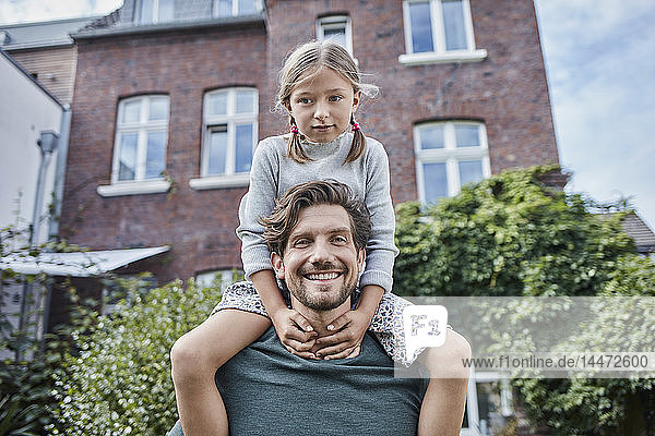 Portrait of happy father with daughter in garden of their home