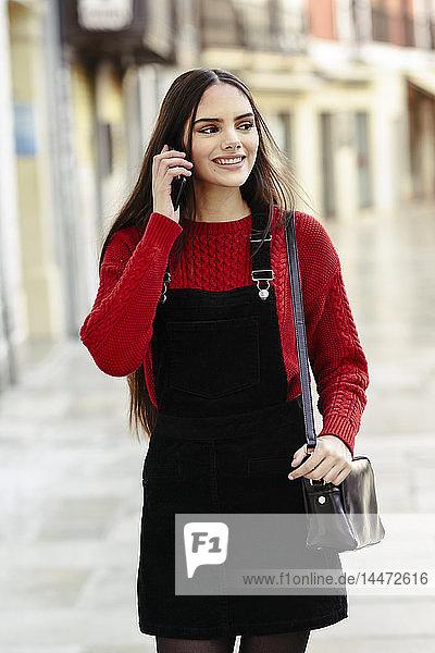 Porträt einer modischen jungen Frau am Telefon