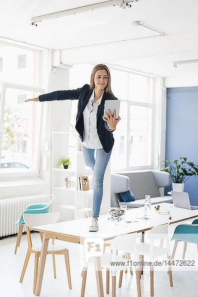Junge Geschäftsfrau balanciert auf einem Bein auf einem Schreibtisch im Sitzungssaal und hält ein digitales Tablett