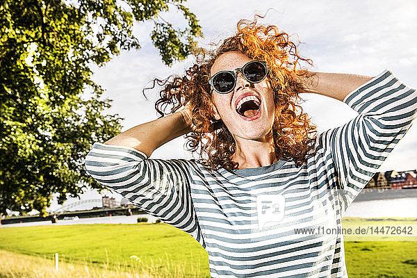 Deutschland  Köln  Porträt einer schreienden rothaarigen jungen Frau mit Sonnenbrille