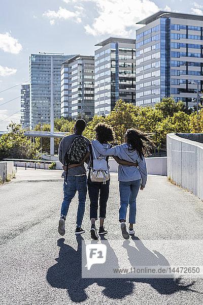 Drei Freunde erkunden die Stadt  gehen Arm in Arm die Straße entlang