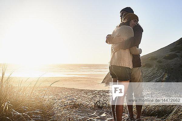 Portugal  Algarve  Paar umarmt sich bei Sonnenuntergang am Strand