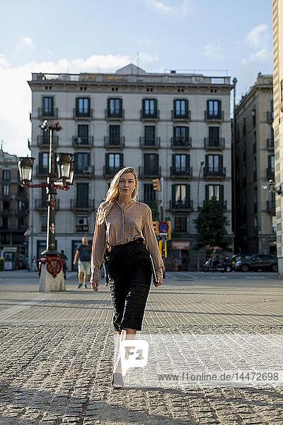 Selbstbewusste junge Geschäftsfrau mit Laptop in der Stadt unterwegs