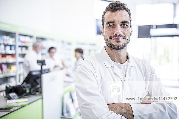 Portrait of smiling pharmacist in pharmacy with colleagues in background