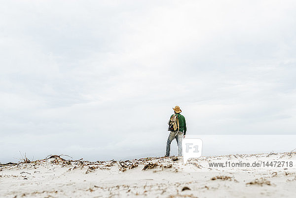 Australia  Tasmania  Maria Island  back view of man with backpack on the beach looking at distance