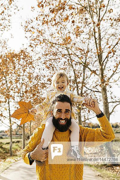 Vater  der seine kleine Tochter morgens im Herbst in einem Park auf den Schultern trägt