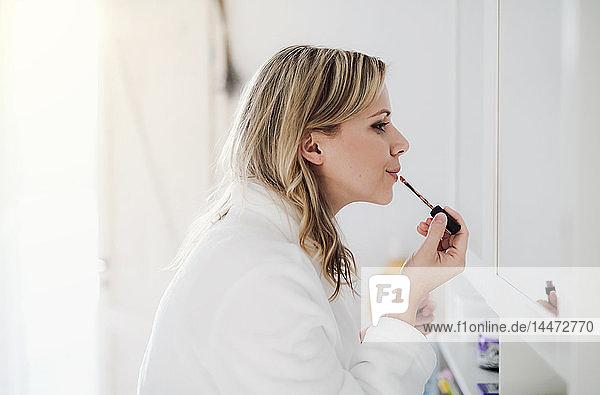 Frau im Bademantel schminkt sich morgens zu Hause