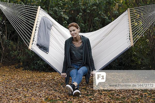 Porträt einer Frau  die im Herbst in der Hängematte im Garten sitzt