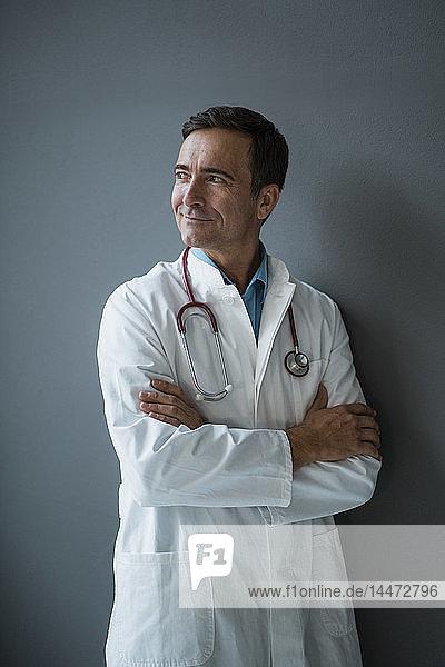 Lächelnder Arzt steht an einer grauen Wand und schaut zur Seite