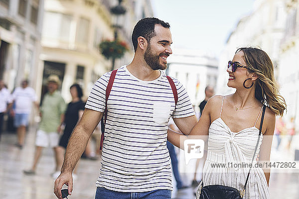 Spain  Andalusia  Malaga  happy tourist couple walking in the city