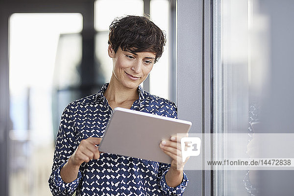 Smiling businesswoman using tablet at the window in office