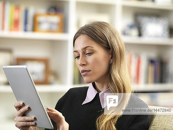Young female relaxing at home using a tablet