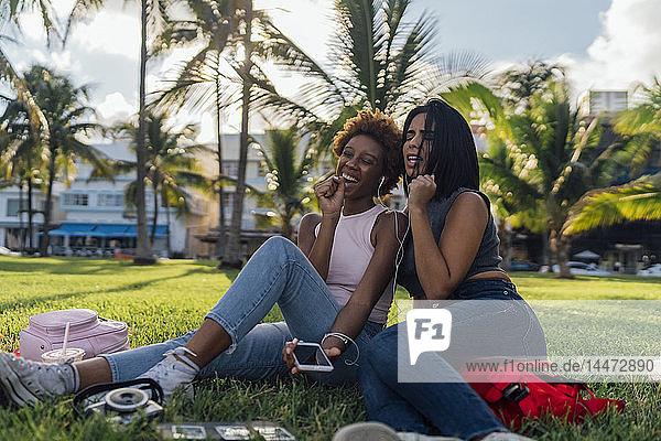 Zwei glückliche Freundinnen entspannen sich in einem Park und hören Musik