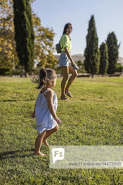 Kleines Mädchen  das mit seiner Mutter auf einem Rasen in einem Park spazieren geht
