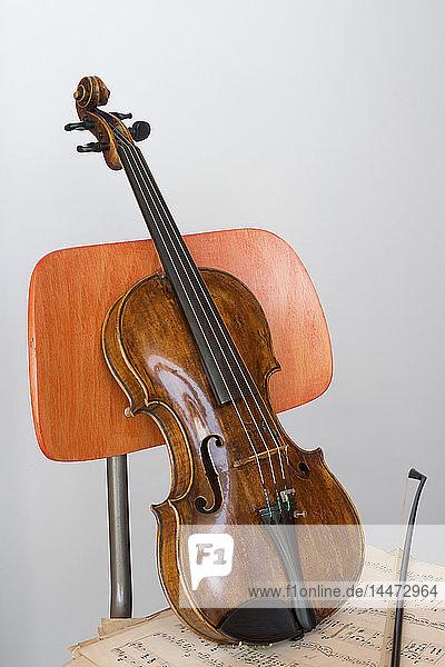 Violine  Bogen und Noten auf Holzstuhl  Nahaufnahme