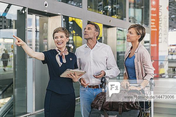 Mitarbeiter einer Fluggesellschaft hilft Ehepaar mit Gepäckwagen auf dem Flughafen