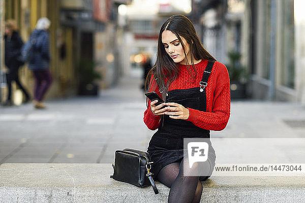 Porträt einer modischen jungen Frau  die auf einer Bank in der Fussgängerzone sitzt und auf ein Handy schaut