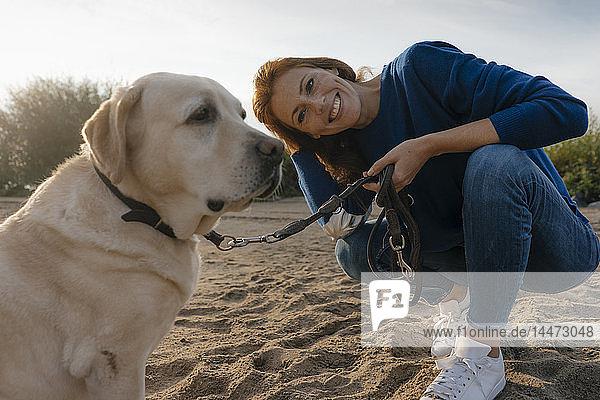 Deutschland  Hamburg  lächelnde Frau mit Hund am Strand am Elbufer