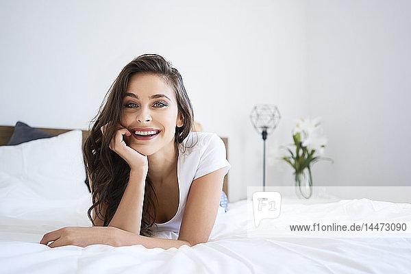 Glückliche junge Frau liegt auf dem Bett und lächelt
