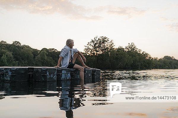 Älterer Mann sitzt bei Sonnenuntergang auf einem Floß in einem See