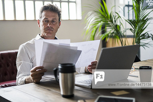 Focused businessman using laptop and reviewing documents at desk