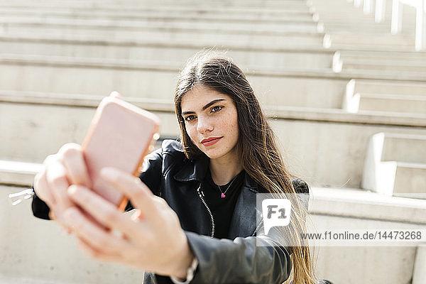 Junge Frau auf der Treppe  die ein Selfie nimmt
